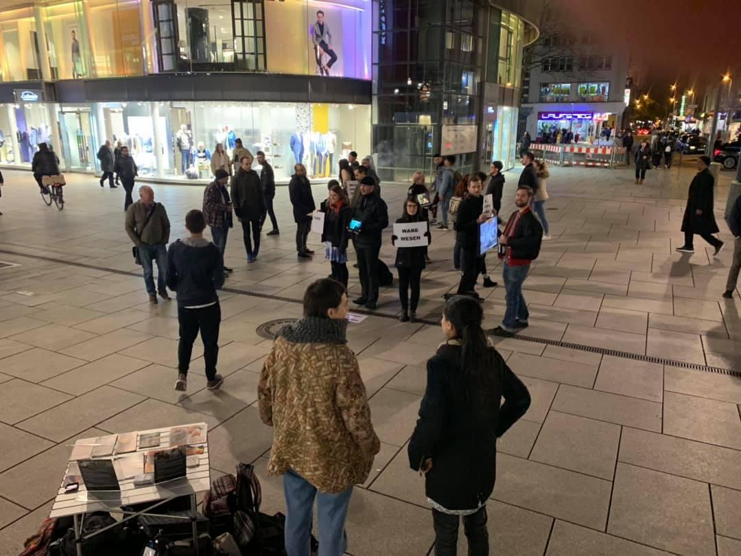In der Mitte stehen Aktivist*innen im Kreis und halten Schilder und Laptops, die die Zustände deutscher Tierhaltung darstellen. Mit den Passant*innen, die sich die Videos anschauen werden Gespräche geführt.